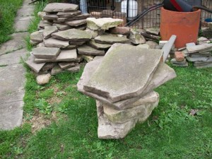 Old sandstone sidewalk stone pieces act as flagstone
