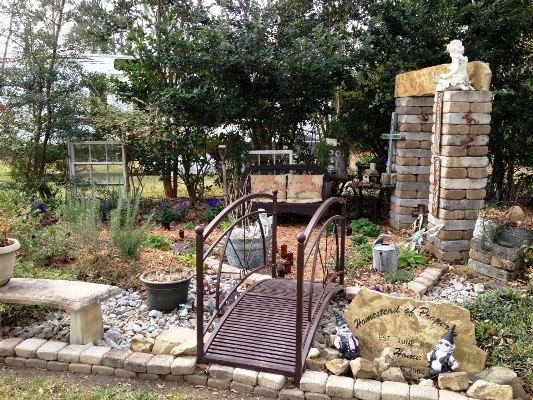 Kathy's bridge crosses over to a stacked stone arbor leading to her butterfly garden. The arbor is watched over by an angel.