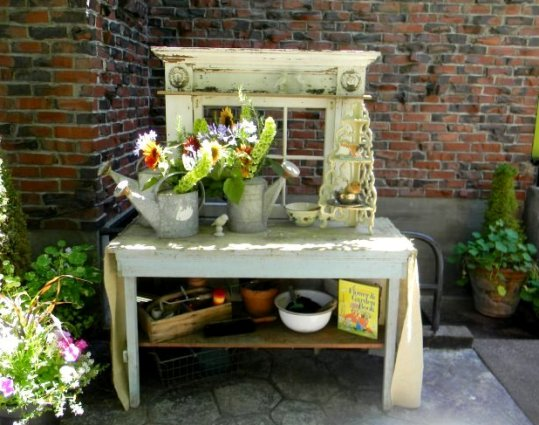 LoriAnne Ross's potting bench.  An old table, a window and a discrd fireplace surround.