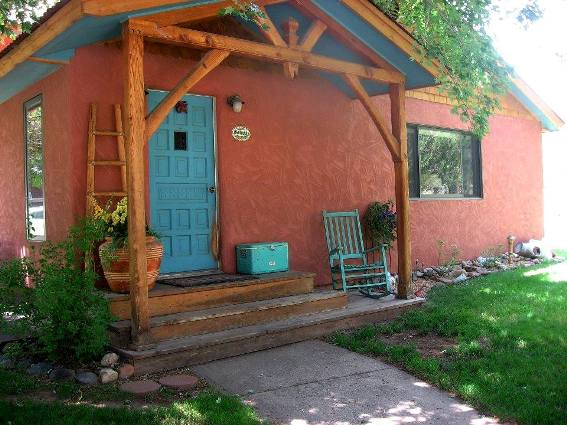 Margaret A Buiso's southwestern style home features a turquoise front door, warm terracotta house color an some rustic treasures as accents.