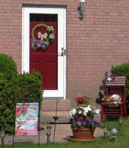 "Nell Howard Stelzer: ""My front entrance with my garden chair and metal junk flag and clay stacked pots."""