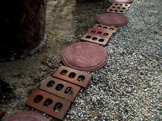 Heavy metal hole covers mix with fancy bricks for a path with some style