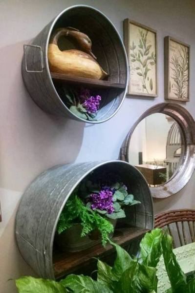 Galvanized tubs are hung on a wall and fitted with shelves and a mirror