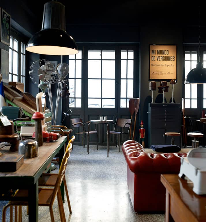 vintage industrial furniture and designer vintage interior by Alketas Pazis: the owner brought together a selection of vintage industrial chairs and tables (wood and metal), a vintage leather couch, vintage industrial lamps and a variety of retro decor items.