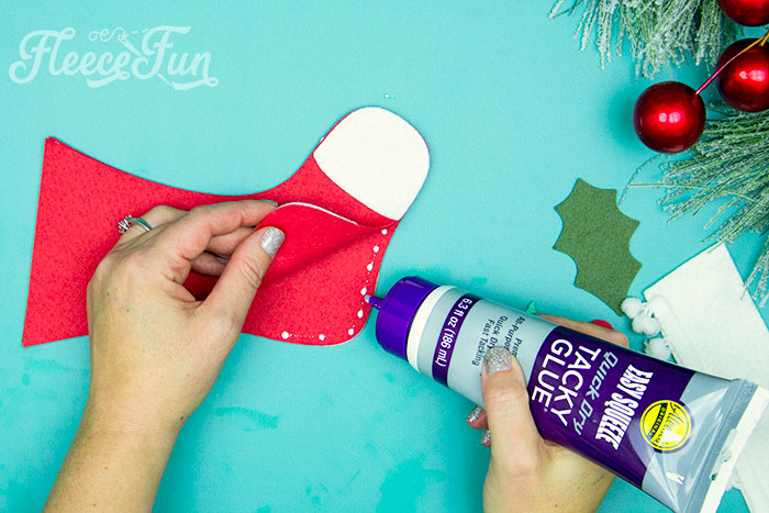 Glueing stocking together. This Felt Stocking Ornament  DIY with FREE template can be sued so any ways! Hand it on the tree, string it from garland or use it to hold a gift card!  The best part about this Christmas tree ornament is that it is No Sew