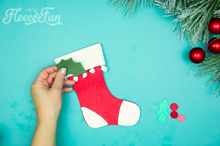 Adding holly to the cuff. This Felt Stocking Ornament  DIY with FREE template can be sued so any ways! Hand it on the tree, string it from garland or use it to hold a gift card!  The best part about this Christmas tree ornament is that it is No Sew