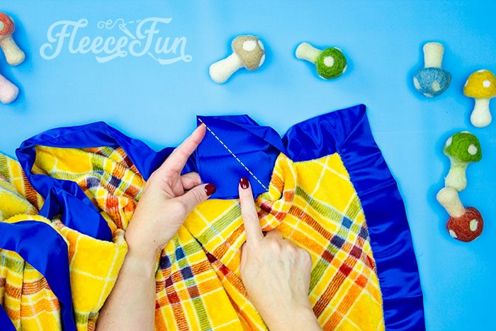Where to sew the binding to bring it together. Learn how to make a fleece blanket with satin binding! This tutorial is a perfect beginning sewing project! Learn how to make mitered corners.