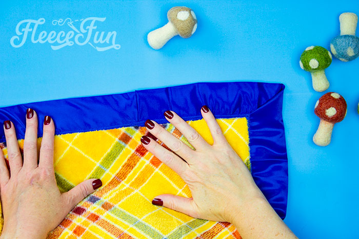 Completed fleece blanket with satin bidning. Learn how to make a fleece blanket with satin binding! This tutorial is a perfect beginning sewing project! Learn how to make mitered corners.