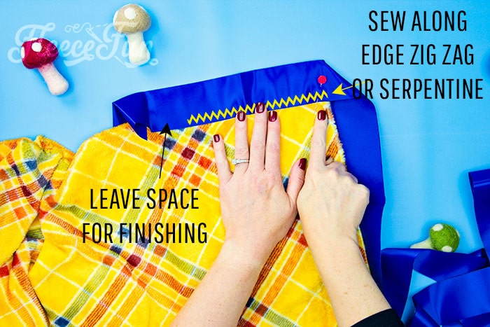 Showing where to start the stitching to begin adding the binding. Learn how to make a fleece blanket with satin binding! This tutorial is a perfect beginning sewing project! Learn how to make mitered corners.