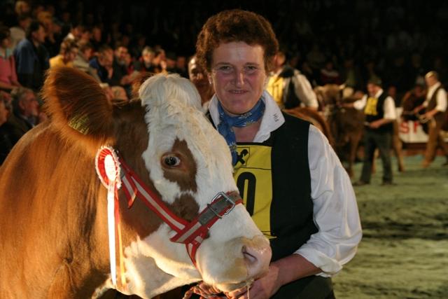 Marianne Wachholbinger mit Bundessiegerin FLORA (V: Horst DE), die mit einem Erbhold-Kalb bei Fuß Bundessiegerin der Rasse Fleckvieh wurde. (Foto: Landwirt.com)