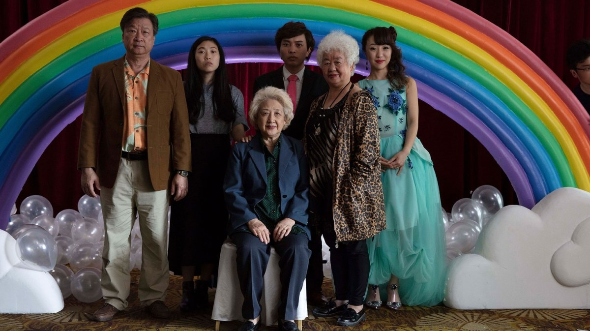 The cast of The Farewell pose for photo with a rainbow