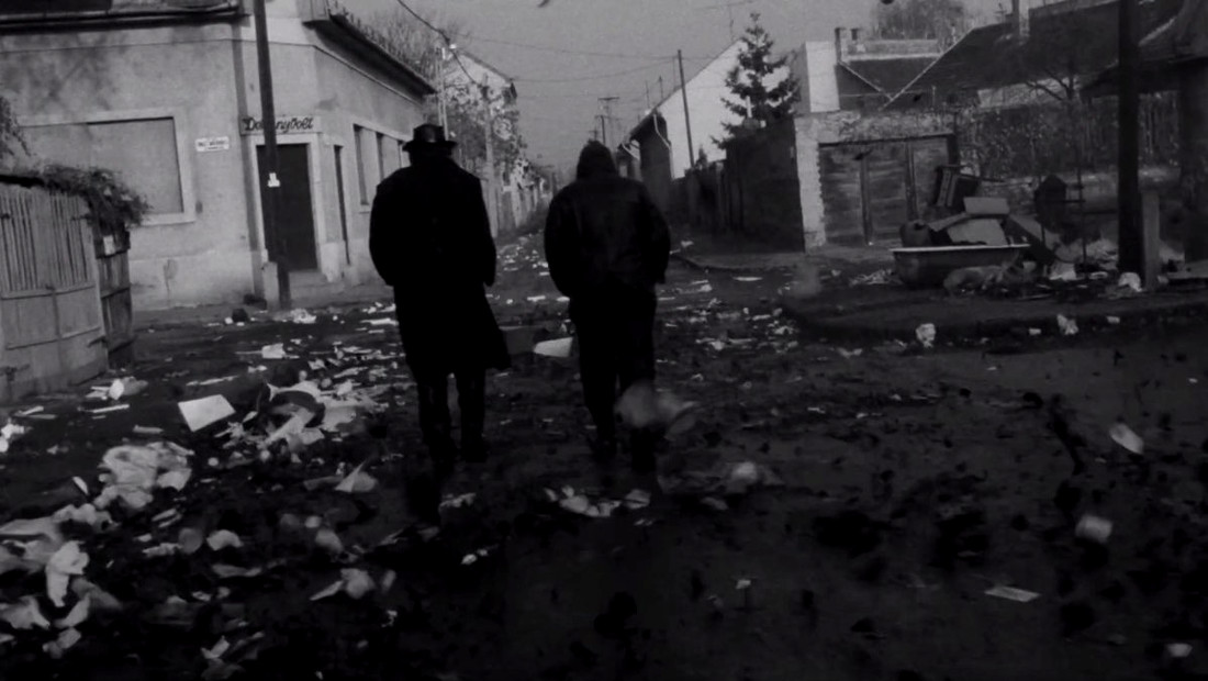 Irimiás walks through wind and trash in Béla Tarr's Sátántangó
