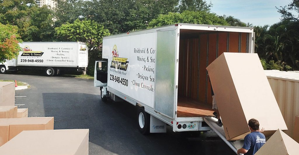 Moving truck with men loading packaged goods for delivery.