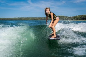 Girl surfing off back of Varatti boat