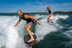 Man and girl are having fun surfing behind the Varatti.