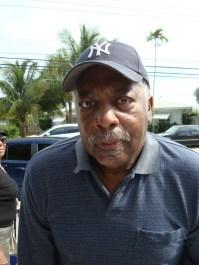 headshot of a black man wearing a NY Yankees baseball cap