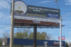 A billboard for Title Credit Finance above a TitleMax storefront shows a picture of a hamster on a wheel and urges borrowers to 'avoid the title pawn treadmill.' Photo: Mitchell Hartman/Marketplace