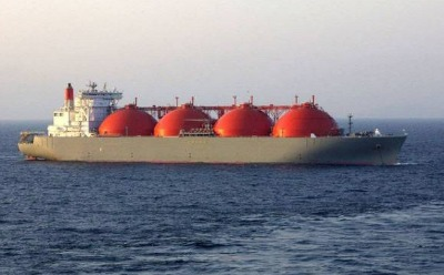 A large tanker ship with giant red, half-ball containers of LNG on the ocean.