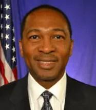 Smiling man with short hair, white shirt, dark jacket, dark patterned tie
