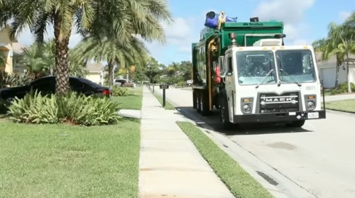 A green and white garbage truck picks up trash at a single-family residence