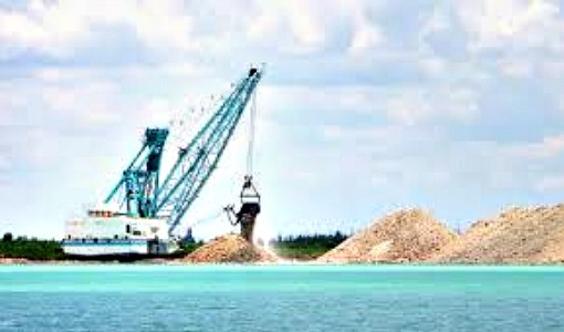 A White Rock dragline excavates blasted limerock into large piles next to bright blue water.