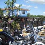 Motorcycles line up in front of the weathered building.