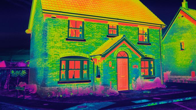 Red and yellow areas of a thermal image show where heat is leaking from a house