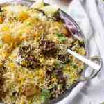 A plate of biryani, ¾ view, sliced cucumber and onions in a small bowl in the back