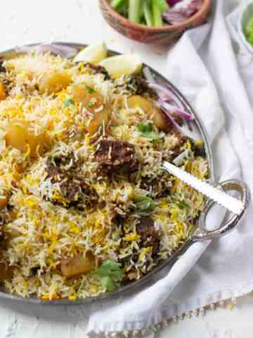 A plate of biryani, 3/4 view, sliced cucumber and onions in a small bowl in the back