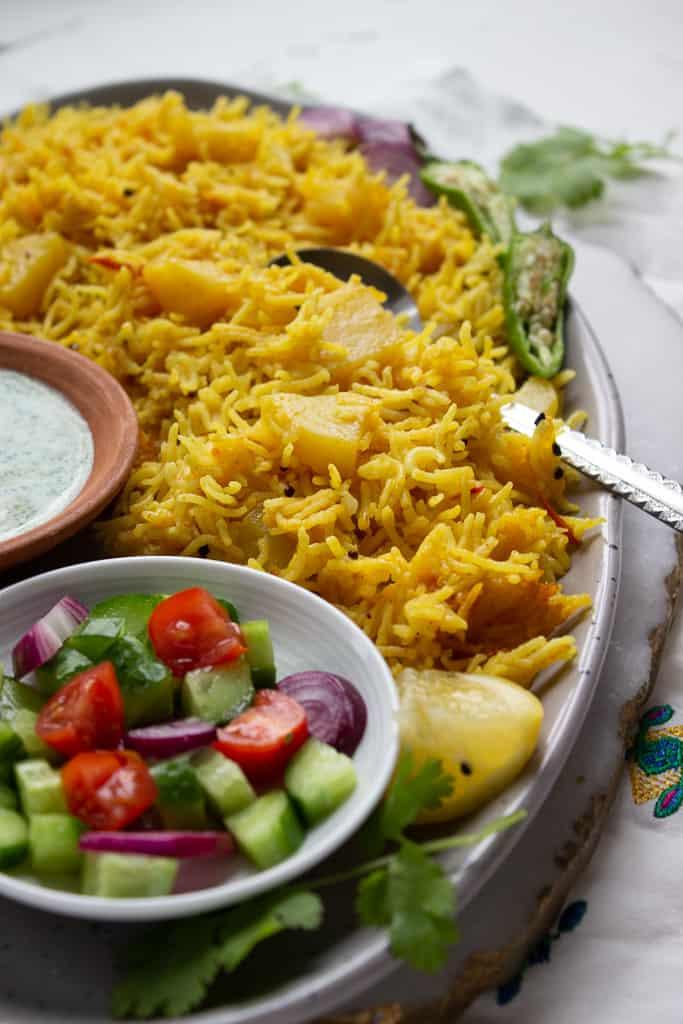 A dish of Tehri with chopped veggies and yogurt chutney
