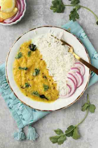 a plate of Khatti Daal with white rice and sliced red onions