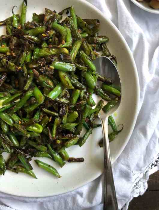 a white plate with lightly charred green beans