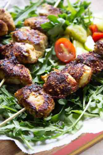 Partial shot of three sesame ginger chicken skewers on a bed of arugula