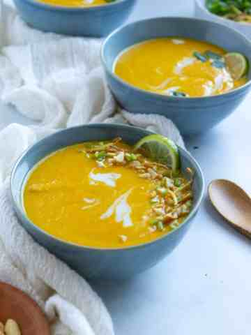 One full and two partial bowls of carrot soup