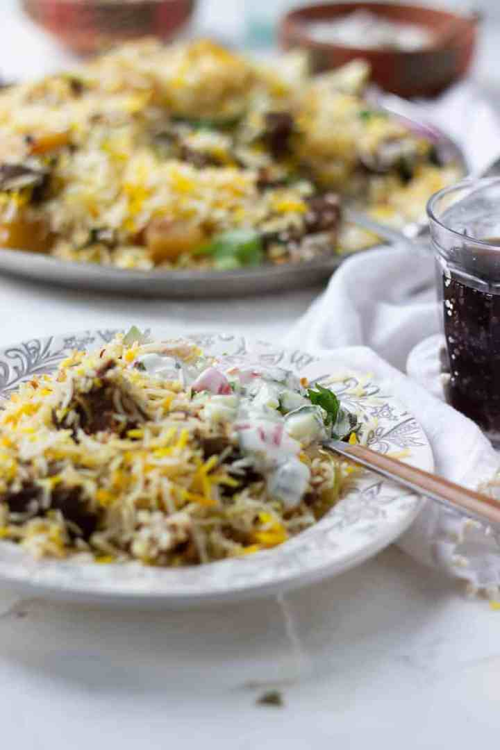Beef Biryani dish in the background and a plate with biryani and raita in the front