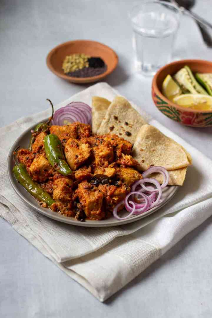 a plate of achar chicken with onions and roti, spices and lemon + chilies in bowls in the background