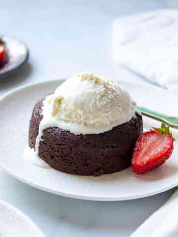 A plate with a lava cake, half a strawberry and melting vanilla ice cream