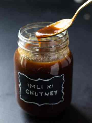 Imli ki Chutney dripping from a spoon back into the jar