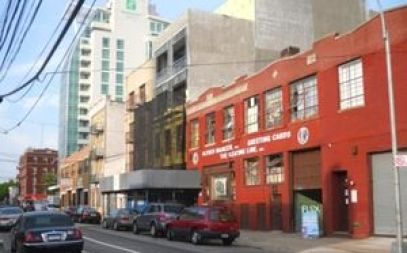 A red brick building beside a taller grey building. In the distance, a green and much taller, off-white colored building looms over the two. The street is lined with cars in front of the two buildings.