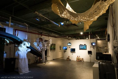A gallery space with monitors lined up on the back wall with a white statue of a hand stands on the left. A large tree painted completely white stands next to the giant hand. A large, beige tapestry with cut outs hangs on the ceiling.