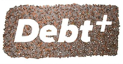 """A collection of coins are gathered together. In the center, the negative space is used to spell out the word, """"Debt +""""."""