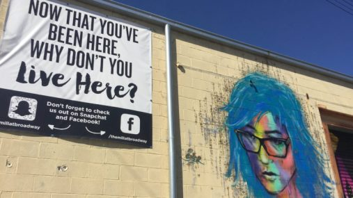 """A sunny wall that looks like the side of a warehouse. Painted on the wall is an image of a woman with blue hair, glasses and a multicolored face. Next to the painting is a sign that says """"Now that you've been here, why don't you live here?"""""""