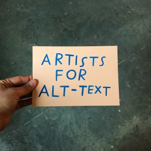 """Image Description: A hand holds up a peach-coloured paper that reads """"Artists for Alt-Text"""" in handwritten, dark blue letters. The background is a marbly, dark green floor."""