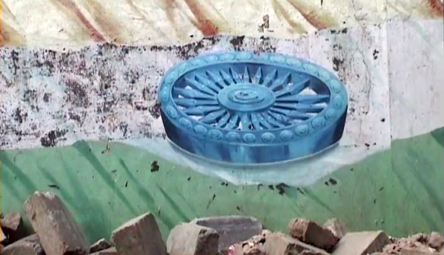 A decaying wall mural of the Indian flag, gold on the top a blue wheel in the middle and green on the bottom, with a pile of rubble and bricks on the bottom.