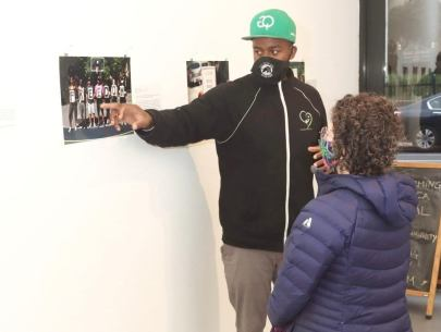 A man wearing a black mask and a green cap points to the side as a woman listens intently at him, behind him is a wall of photos at his exhibition.