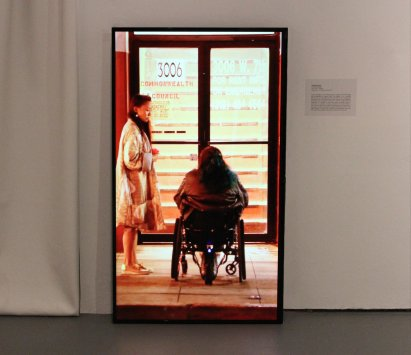 A photo of a person's back sitting in a wheelchair as they interact with someone in front of the Commonwealth Council. Behind the double doors are a flight of stairs.