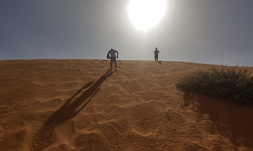 Sun Setting In The Desert Sands Of Niamey With Two Crew Members Climbing The Mountain Sands