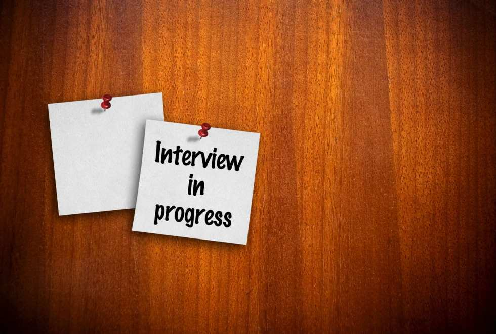 Picture of a note on a door saying, 'Interview in progress'.