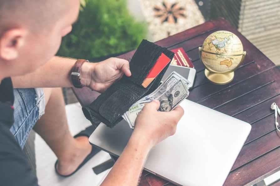 man holding u s dollar banknotes and black leather bi fold wallet