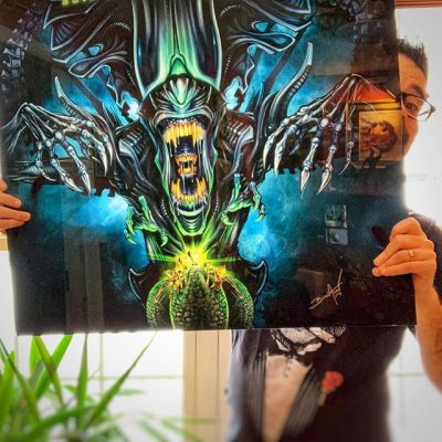 "Check out the size of my Alien Pinball Backglass! Message me if you want one! A while back, I was commissioned to create a backglass for the official Alien pinball machine. But due to a gypsy curse, the company fell apart before these could be massively produced, and I never received the backglass I was promised (frowny face). But I ran into a company that produced one for me after all this time, and it's so cool! It's printed on 1/8"" thick translucent acrylic, so light shines through it. I need to build a lightbox for it.We made a couple if anyone wants one.#alien #pinball #backglassart #alienpinball #translite"
